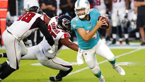 Dolphins quarterback Ryan Fitzpatrick scrambles away from Atlanta's Jack Crawford last August.