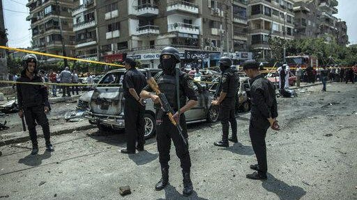 Egyptian policemen stand guard at the site of a bombing that killed Egypt's top prosecutor, Hisham Barakat, who oversaw cases against thousands of Islamists, on June 29, 2015, in Cairo.