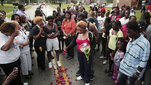 Lezley McSpadden, center, drops rose petals on the bloodstains from her son Michael Brown, who was shot and killed by a police officer in the middle of the street Aug. 9, 2014, in Ferguson, Mo.