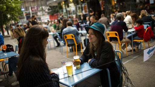 Customers drinks beers at the terrace of the Bar du Matin restaurant in Brussels. Alex Van Tuijn, co-owner of four cafes in Brussels, has found that staying in business during a pandemic can mean sacrificing some of the very things a company is known for.