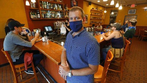 Nick Gavrilides, owner of the Soup Spoon, poses at the restaurant in Lansing, Mich. on July 16. Thousands of restaurants, bars and other merchants have filed insurance claims for business interruption. Most claims have been denied.