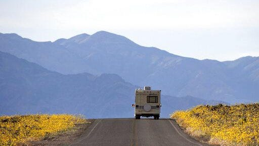 FILE - In this Feb. 24, 2016, file photo, wildflowers bloom as an RV travels along the road near Badwater Basin in Death Valley, Calif. Heading out on a road trip in a recreational vehicle allows travelers a unique opportunity to explore the nation while enjoying some comforts, too.
