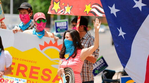 "Democratic congressional candidate Teresa Leger Fernandez, in the blue mask, cheers on supporters at a polling station Tuesday, June 2, 2020, in Santa Fe, N.M. Fernandez was flanked by her three sons, left to right, Alisandro, Dario and Abelino. The sign she holds, ""Ahora es cuando,"" is Spanish for ""Now is the time."""