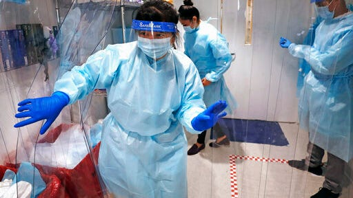 Lena Landaverde, assistant director of the Precision Diagnostics Center, heads to the new COVID-19, on-campus testing labs after donning personal protective equipment, Thursday, July 23, 2020, at Boston University in Boston. Dozens of U.S. colleges are announcing plans to test students for the coronavirus this fall, but their strategies vary widely. Federal health officials discourage widespread testing on college campuses, but some researchers say it's necessary to prevent outbreaks.