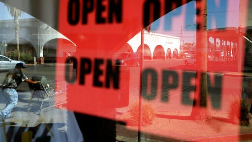 FILE - In this June 30, 2020, photo, a man passes a clothing shop with open signs in the window in Calexico, Calif. Records obtained by The Associated Press show governors working closely with business interests as they weighed when and how to reopen their economies during the coronavirus pandemic.