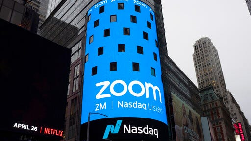 FILE - This April 18, 2019, file photo shows a sign for Zoom Video Communications ahead of the company's Nasdaq IPO in New York. Now that Zoom has emerged as one of the most popular ways to get together virtually while the coronavirus pandemic keeps people apart, the company is trying to build a more secure fortress around the billions of conversations occurring on its videoconferencing service daily.