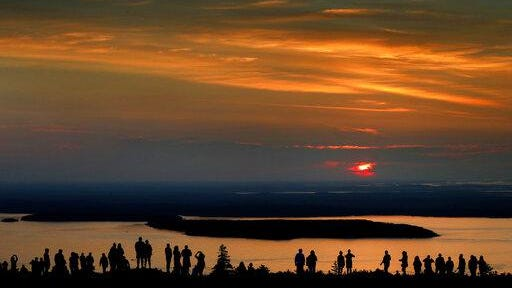 A crowd of early-risers gather near the summit of Cadillac Mountain in Acadia National Park on July 31, 2018, to be among the first in the continental United States to see the sunrise, near Bar Harbor, Maine.
