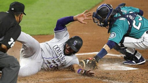 Colorado's' Elias Diaz slides safely across home as Seattle catcher Austin Nola puts on a late tag in the third inning on Friday in Seattle.