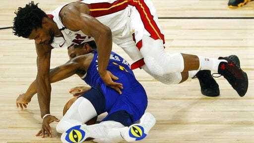Monte Morris, bottom, of the Denver Nuggets, loses the ball against Jimmy Butler of the Miami Heat at HP Field House at ESPN Wide World Of Sports Complex on Saturday in Lake Buena Vista, Fla.