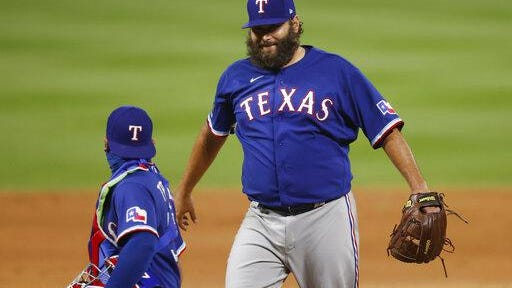 Texas Rangers starting pitcher Lance Lynn, back, celebrates with catcher Jose Trevino after Lynn retired Colorado Rockies' Nolan Arenado for the final out in the ninth inning of a baseball game Friday, Aug. 14, 2020, in Denver. Texas won 3-2.