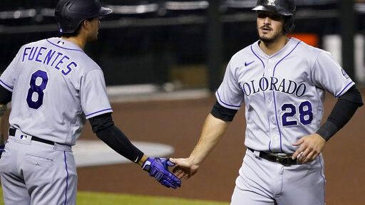 Colorado Rockies' Nolan Arenado, right, is greeted by Josh Fuentes after scoring on a base hit by Matt Kemp during the first inning on Tuesday at Chase Field in Phoenix.