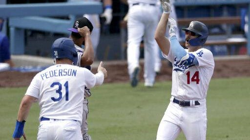 Los Angeles Dodgers' Enrique Hernandez, right, celebrates with Joc Pederson, front left, after hitting a three-run home run as Colorado Rockies catcher Elias Diaz looks away during the fourth inning on Sunday at Dodgers Stadium in Los Angeles.