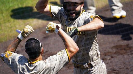 San Diego Padres' Eric Hosmer, back, celebrates hitting a three-run home run with Manny Machado in the first inning on Sunday against the Colorado Rockies at Coors Field in Denver.