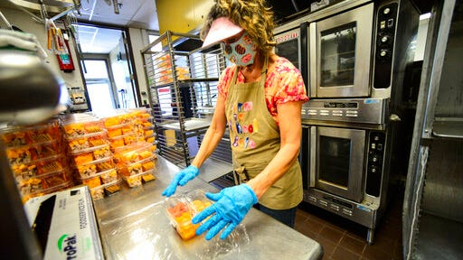 Pam Kissell, a food service worker at the Bellows Falls Union High School, in Westminster, Vt., wraps meals to be handed out to students as part of the Windham Northeast Supervisory Union summer meals program on Friday, Aug. 7, 2020.