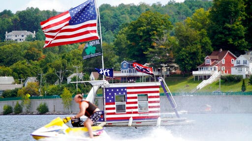 A jet skier passes a patriotic shanty-boat owned by AJ Crea on Pontoosuc Lake on Labor Day in Pittsfield, Mass., Monday, Sept. 7, 2020.