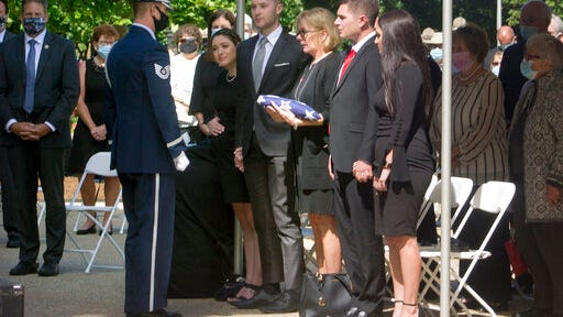 Heather Merrill, widow of former Gov. Steve Merrill, receives an American flag at his memorial service outside the Statehouse on Friday, Sept. 11, 2020, in Concord, N.H. Merrill, a Republican who served two terms in the 1990s, died Sept. 5 at age 74.