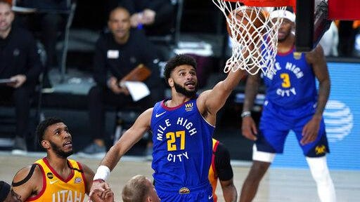 Denver Nuggets' Jamal Murray, right, goes up for a shot against the Utah Jazz during the first half of an NBA basketball first round playoff game Sunday in Lake Buena Vista, Fla.