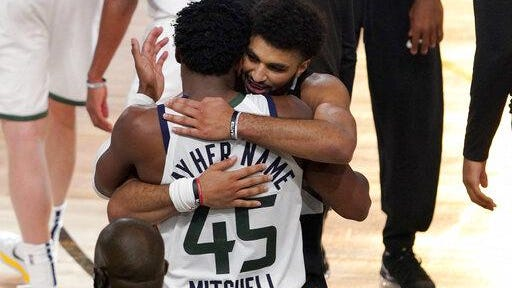Utah Jazz's Donovan Mitchell, foreground, and Denver Nuggets' Jamal Murray greet each other after their NBA first round playoff basketball game on Tuesday in Lake Buena Vista, Fla. The Nuggets won 80-78.