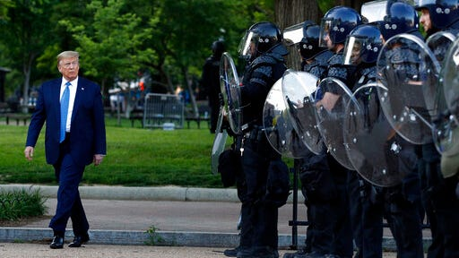 President Donald Trump walks past police in Lafayette Park after he visited outside St. John's Church across from the White House Monday, June 1, 2020, in Washington. Part of the church was set on fire during protests on Sunday night.