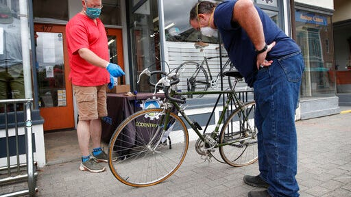In this Tuesday, June 9, 2020 photo, Harvey Curtis, left, discusses repair plans with customer Jack Matheson outside Sidecountry Sports, a bike shop in Rockland, Maine. Matheson is looking forward to getting his 40-year-old Raleigh back on the road.