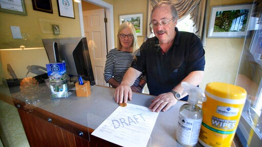 """In this Wednesday, June 10, 2020, photo, Cod Cove Inn owners Ted and Jill Hugger show a draft of a compliance form that inn owners may be required to have out-of-state guests sign before being allowed to check in at their inn in Edgecomb, Maine. The form is part of the """"Keep Maine Healthy"""" plan the state is proposing to help prevent the spread of the coronavirus. Residents of New Hampshire and Vermont would be exempt."""