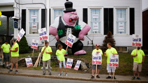 Strikers picket outside the district lodge of Local 6 across from Bath Iron Works, Monday, June 22, 2020, in Bath, Maine. Production workers at one of the Navy's largest shipbuilders overwhelmingly voted to strike, rejecting the company's three-year contract offer Sunday and threatening to further delay delivery of ships.