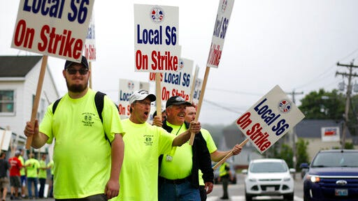 Picketers acknowledge a honking motorist outside an entrance to Bath Iron Works, Monday, June 22, 2020, in Bath, Maine. Production workers at one of the Navy's largest shipbuilders overwhelmingly voted to strike, rejecting the company's three-year contract offer Sunday and threatening to further delay delivery of ships.