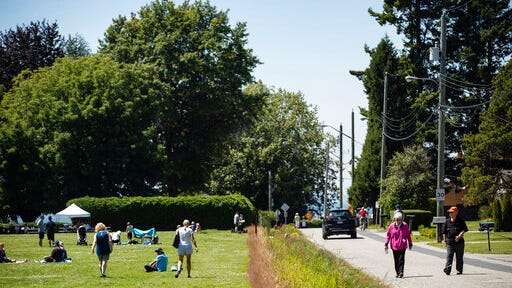 A ditch marks the Canada-U.S. border and separates people walking on the road, right, in Surrey, British Columbia, and those gathered at Peace Arch Historical State Park, left, in Blaine, Wash., Sunday, July 5, 2020. Although the B.C. government closed the Canadian side of the park in June due to concerns about crowding and COVID-19, people are still able to meet in the U.S. park due to a treaty signed in 1814 that allows citizens of Canada and the U.S. to unite in the park without technically crossing any border.