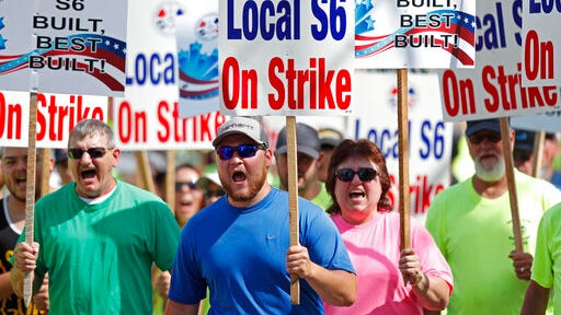 FILE - In this July 25, 2020 file photo, striking Bath Iron Works shipbuilders march in solidarity in Bath, Maine. A 63-day strike at Bath Iron Works -- against the backdrop of a pandemic in an election year -- came to an end Sunday, Aug. 23 with shipbuilders voting to return to their jobs producing warships for the United States Navy.