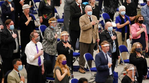 Members of the New Hampshire House of Representatives stand for the Pledge of Allegiance at the start of their session in Durham, N.H. on Thursday, June 11, 2020, at the Whittemore Center at the University of New Hampshire. The Legislature, which has held numerous sessions in the arena in 2020 due to the coronavirus pandemic, is scheduled to hold a session Wednesday, Dec. 2 on an outdoor field at UNH.