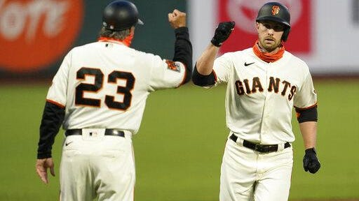 San Francisco's Austin Slater, right, celebrates with third base coach Ron Wotus after hitting a solo home run against Colorado during the first inning on Tuesday in San Francisco.