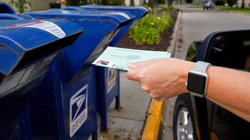 FILE - In this Tuesday, Aug. 18, 2020, file photo, a person drops applications for mail-in-ballots into a mailbox in Omaha, Neb. Data obtained by The Associated Press shows Postal Service districts across the nation are missing the agency's own standards for on-time delivery as millions of Americans prepare to vote by mail.