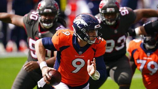 Denver quarterback Jeff Driskel scrambles under pressure from Tampa Bay nose tackle Vita Vea, left, and defensive end Ndamukong Suh, right, during the first half on Sunday at Empower Field at Mile High in Denver.