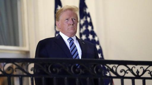 President Donald Trump stands on the balcony outside of the Blue Room as returns to the White House Monday after leaving Walter Reed National Military Medical Center, in Bethesda, Md.