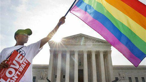 Carlos McKnight of Washington, waves a flag in support of gay marriage outside of the Supreme Court in Washington, Friday June 26, 2015. A major opinion on gay marriage is among the remaining to be released before the term ends at the end of June.