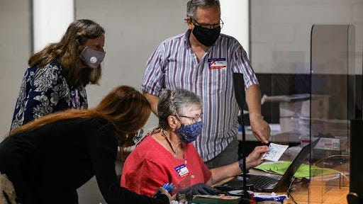 Poll workes gather around Rosemary Spatafora while wearing masks to assist her in spoiling an absentee ballot during the Michigan primaries at the community center in Pleasant Ridge, Mich. on Aug. 4, 2020.