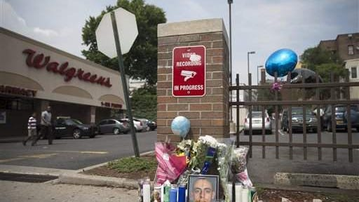 A memorial for 23-year-old Jersey City police officer Melvin Santiago stands at the Walgreens where he was fatally shot on Sunday in Jersey City.  (AP Photo/John Minchillo)