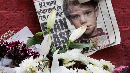 This May 28, 2012, file photo shows a newspaper with a photograph of Etan Patz that is part of a makeshift memorial in the SoHo neighborhood of New York. While Pedro Hernandez told police he choked 6-year-old Patz in 1979, his defense said it was fiction from a man with an IQ in the bottom 2 percent of the population and mental illness that makes it difficult for him to distinguish real life from fantasy.