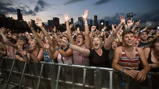 FILE - This Aug. 3, 2013 file photo shows fans reacting while Mumford & Sons performs at the Lollapalooza Festival in Chicago. Lollapalooza marks its 10th anniversary in Chicago when it opens for three days starting Friday, Aug. 1, 2014, with a lineup including Eminem, Outkast and Kings of Leon. Lollapalooza became the basis for the modern festival culture and circuit that has evolved since, including events like Bonnaroo, Coachella and a legion of smaller multi-day parties.