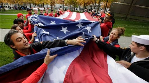 Volunteers with the veterans advocacy group Team Red White and Blue unfurl a large American flag at the National September 11 Memorial on Sunday in New York.