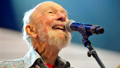 FILE - This Sept. 21, 2013, file photo shows Pete Seeger performing on stage during the Farm Aid 2013 concert at Saratoga Performing Arts Center in Saratoga Springs, N.Y.