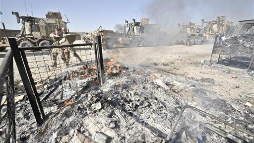 A British soldier from 1 Mechanized Brigade throw rubbish onto a burn pit in the Nahr-e Saraj district, Helmand Province, Afghanistan, on Oct. 1, 2013.