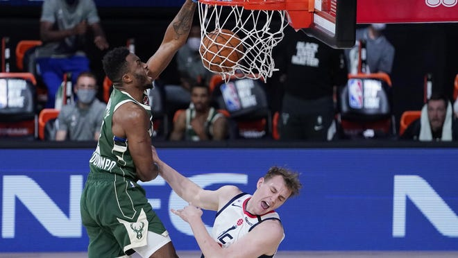 Milwaukee Bucks' Thanasis Antetokounmpo, left, slams a dunk over Washington Wizards' Anzejs Pasecniks (18) during the second half of an NBA basketball game, Tuesday, Aug. 11, 2020, in Lake Buena Vista, Fla.