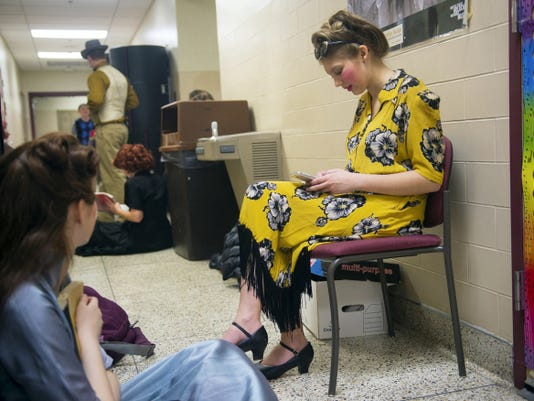 Ensemble cast member Tori Light checks her phone before a rehearsal run-through at Hanover High School on April 7.