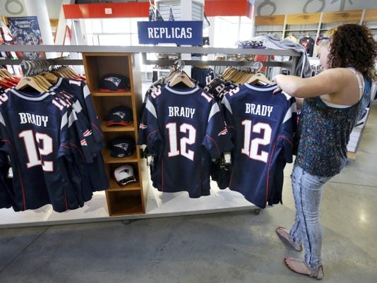 Miguelina Huertas of Worcester, Mass., right, examines jerseys featuring the name and number of New England Patriots football quarterback Tom Brady in the ProShop at Gillette Stadium on Wednesday in Foxborough, Mass. Brady is expected to appeal his suspension by the NFL for his role in the deflating of footballs.