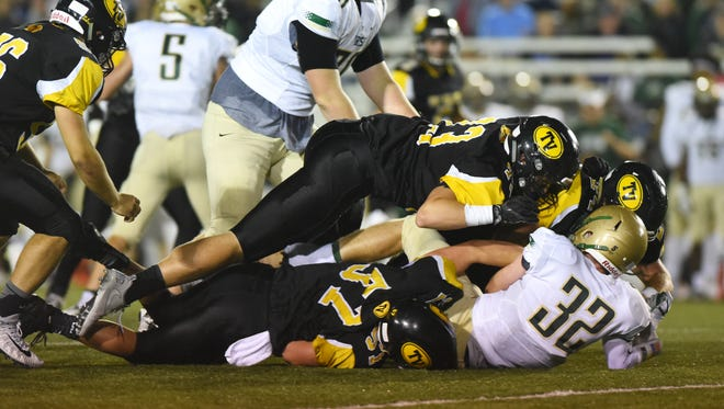 A host of Tri-Valley defenders tackle St. Vincent-St. Mary's Tyler Lattea.