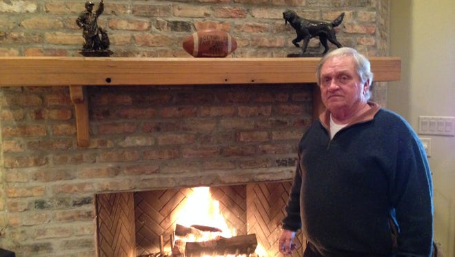 Butch Crenshaw warms up on a recent cold day by the fireplace in his home. The football on the mantel is the game ball he received as a guard/linebacker for Bolton after a Bears' victory over Fair Park in his senior season.