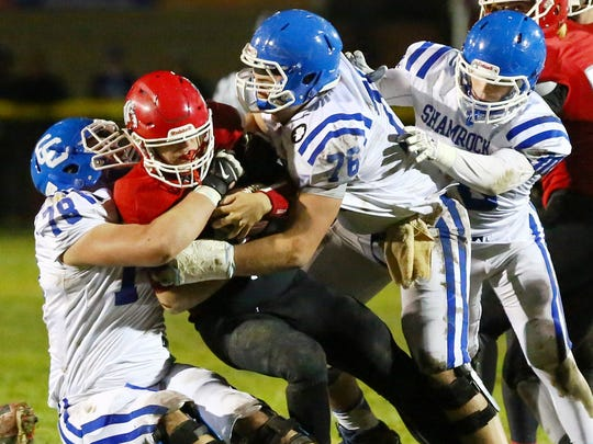Catholic Central's Tom Kowalkoski (left) and Blake Bueter (right) converge to make the tackle on a Romeo ball carrier.