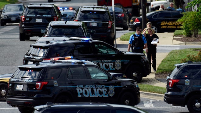 Police secure the scene of a shooting at the building housing The Capital Gazette newspaper in Annapolis, Md., on June 28, 2018.