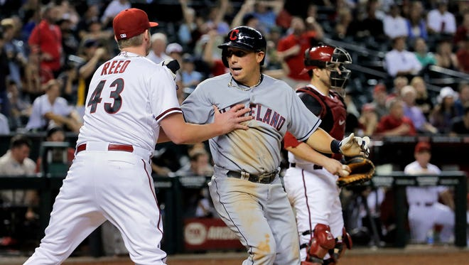 Cleveland Indians' Asdrubal Cabrera collides with Diamondbacks pitcher Addison Reed (43) as Miguel Montero looks away after Cabrera scored during the ninth inning of a baseball game, Tuesday, June 24, 2014, in Phoenix.